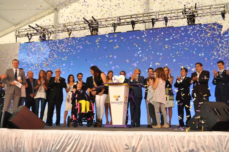 Teletón and Univision representatives and families join Iris and Sofia Urrútia as they open their present, a TeletónUSA plaque that officially opens CRIT USA. Photo by Iris Dimmick.