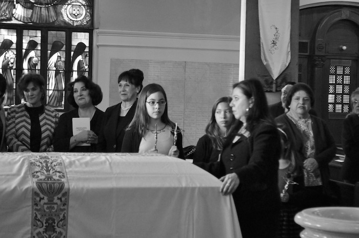 Friends and family of Elvira Munguia Cisneros (1924 - 2014) look on during the entrance processional of her Catholic funeral Mass. Photo by Iris Dimmick.
