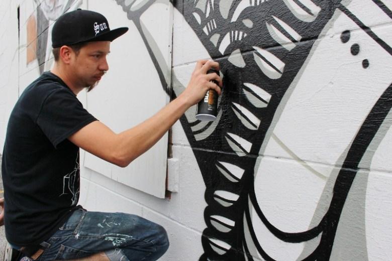 Shek Vega spray painting a mural for Luminaria 2014. Photo by Page Graham.