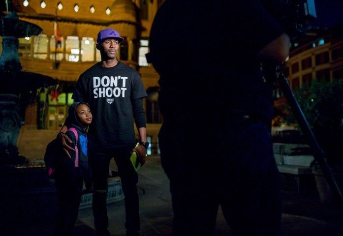 Mike Lowe and his daughter prepare for an interview at the SATX4Ferguson protest. Photo by Scott Ball.