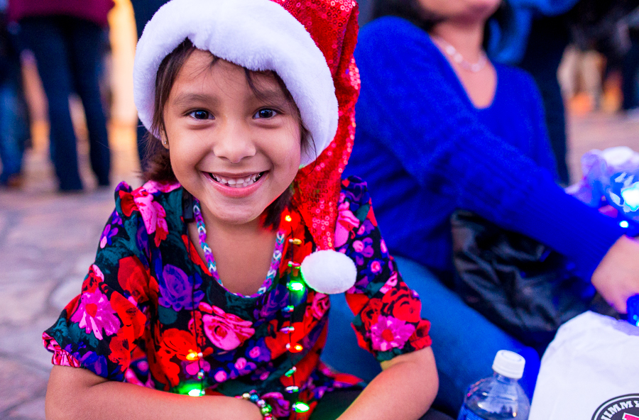 A child named Leah poses for a photo at the H-E-B Tree Lighting Ceremony. Photo by Scott Ball.