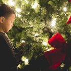 A boy inspects the Christmas tree at the Travis Park tree lighting in November 2014. Photo by Scott Ball.