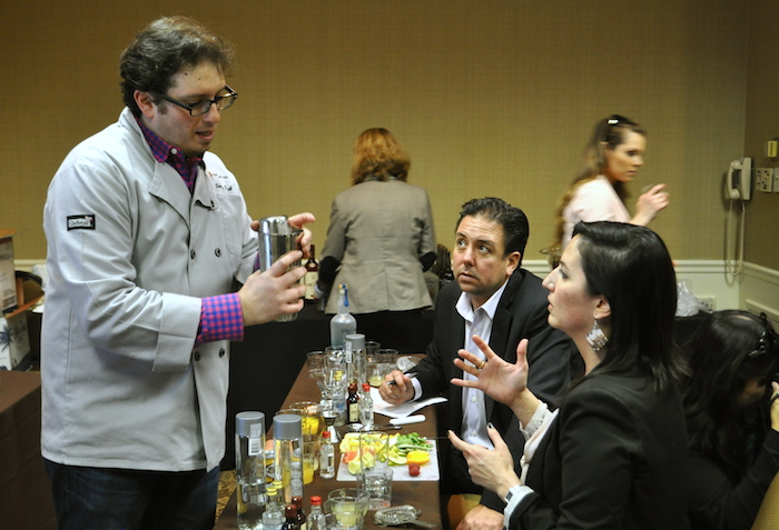 """Jonathan Pogash, The Cocktail Guru, demonstrates proper cocktail shaking technique to students at his seminar, """"Mixology 101,"""" during the 2014 San Antonio Cocktail Conference. Photo by Iris Dimmick."""