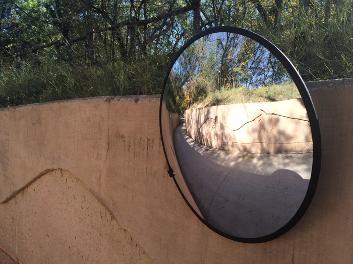 A mirror provides a view of any approaching cyclists or pedestrians along the Leon Creek trail. Photo by Katherine Nickas.