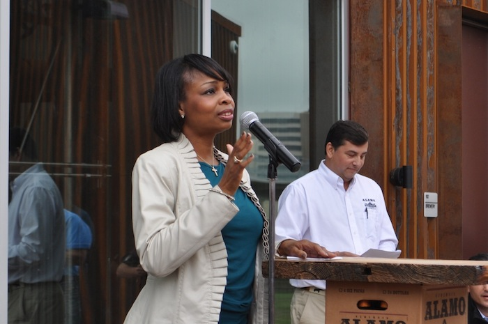 Mayor Ivy Taylor speaks to the large crowd gathered at the brewery's ribbon cutting ceremony as well as the handful of protestors on the Hays Street Bridge. Photo by Iris Dimmick.