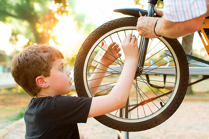 A child learns about adjusting tires during a Earn-A-Bike BScuela session. Photo by Rachel Chaney