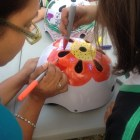 A mother and daughter decorate the daughter's bike helmet at Earn-a-Bike, Day One. Photo by Lily Casura.