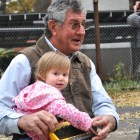 Edgar Dodson holds his granddaughter, Julianna, while he watches his team move the Boehler House. Photo by Iris Dimmick.