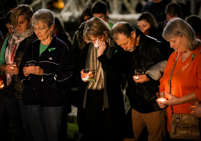 Valerie and Mickey Redus (center) bow their heads in tearful prayer during a candlelight vigil on the one year anniversary of Cameron Redus' death. Photo by Scott Ball.