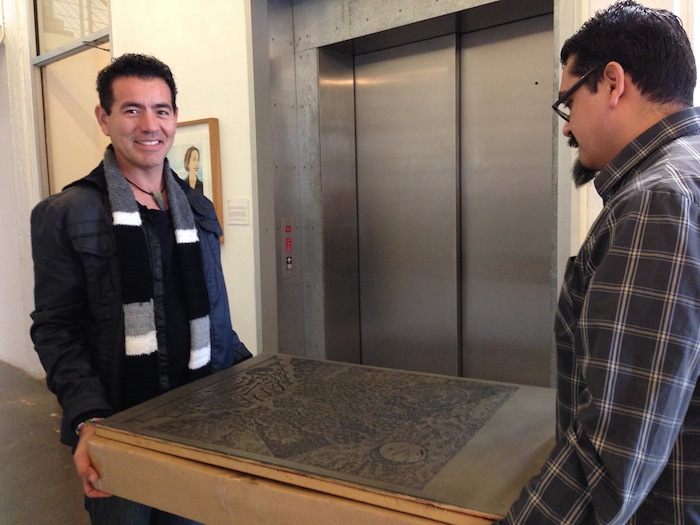 Artpace Education Ambassadors Ernesto Olivo and Ramon Munoz carry a woodcut plate by Ricky Armendariz donated by Hare & Hound Press to teach students about printmaking. Photo by Wendy Atwell.
