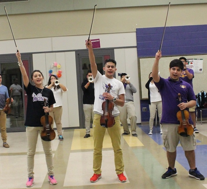 Brackenridge High School Mariachi Aguila students (from left) Ariana Garza, Oscar Garza and Raymond Nieto strike a final pose with their violins as they finish performing their competition piece. Photo by Amanda Lozano.