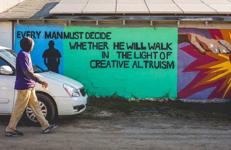 A man walks by a mural during the 2015 MLK March.  Photo by Scott Ball.