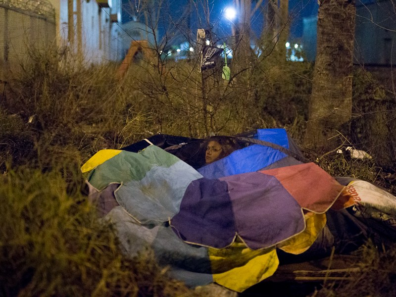 A woman peers from the roof of her shelter during the point-in-time count of the local homeless population put on by local police and Haven for Hope. Photo by Scott Ball.