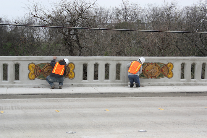Artists help Diana Kersey install her ceramic panels along the Houston Street bridge. Photo by Kay Richter.
