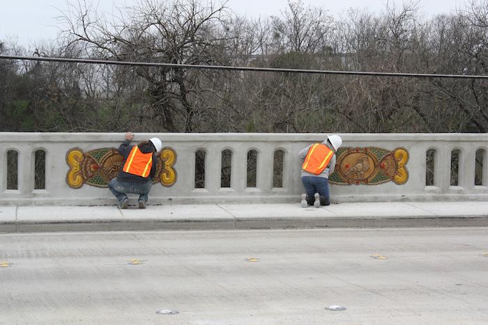 Artists help Diana Kersey install her ceramic panels along the Houston Street bridge. Photo by Kay Richter.