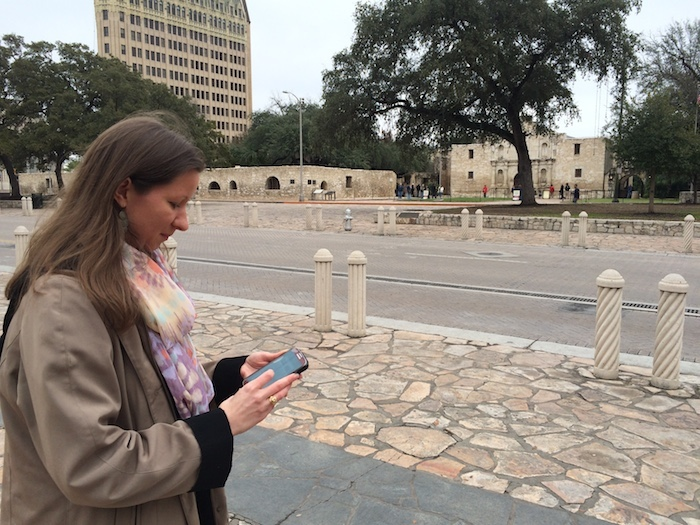 enny Hay, preservation outreach manager with the San Antonio Conservation Society, uses the Texas Star Trail mobile app to explore features of Alamo Plaza. Photo by Katherine Nickas.