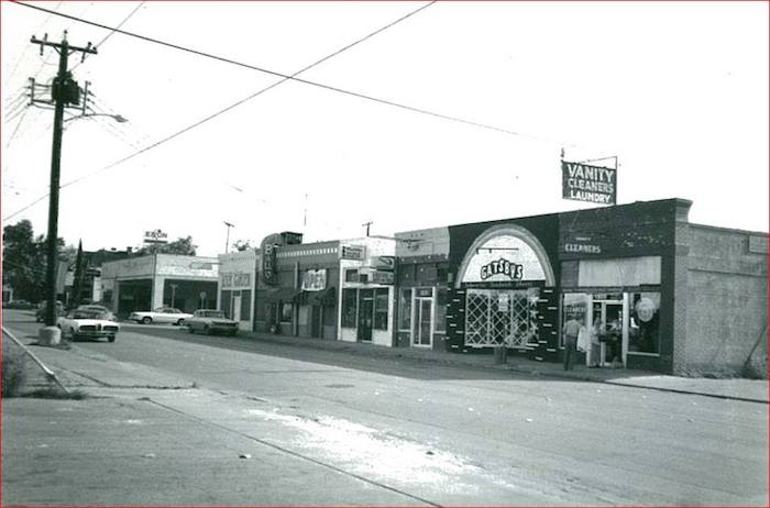 This is the view of the 1800 block of Main Avenue, looking south. A dusty front window peered into Vanity Cleaners. Gatsby's Sandwich Shoppe had an upper level built from recycled wood. A Mod Clothing store was next door. The Aladdin Poodle Parlor served the peacocky pooches of Monte Vista. Ball-It was a pinball arcade. It was so popular that the Rock Garden Nightclub next door became Eat-It, a bar & grill. An Exxon sign hangs above an old gas station. Through the peeling and faded paint, one could discern a previous occupant, Hudson Cars. Gas-guzzling muscle cars (Mercury, Chevrolet, Oldsmobile) cruise the street. Photo by Don Mathis.