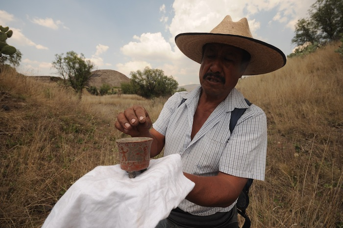 Luis, displaying a ceremonial incense bowl he discovered in a cave, is a farmer who came to talk when he saw me hunting for arrowheads near the pyramids. He congratulated me on my find and told me I was very lucky. Photo by Everett Redus.