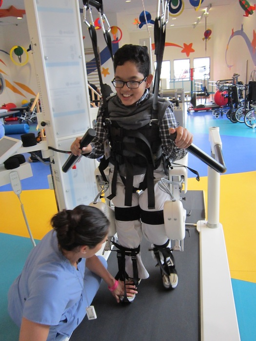 """Freed from his wheelchair, Andy Sosa, 10, is able to walk with the help of his """"robot"""" and physical therapist Cynthia Alfaro."""