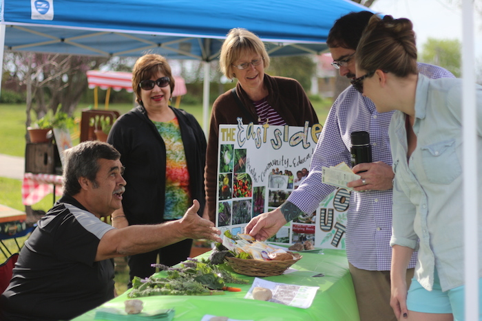 Bruce Dailey from the Green Spaces Alliance gives attendees free seed packets at the Dignowity Hill Farmer's Market.