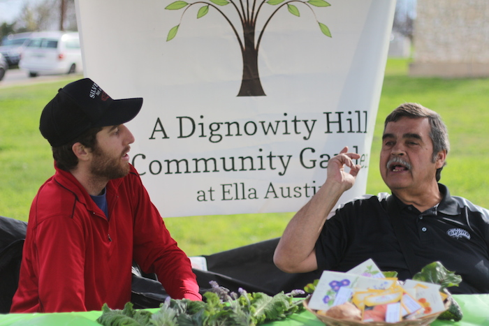 Green Spaces Alliance members Ryan Bigley and Bruce Dailey sit behind their booth at the Dignowity Hill Farmer's Market grand opening.