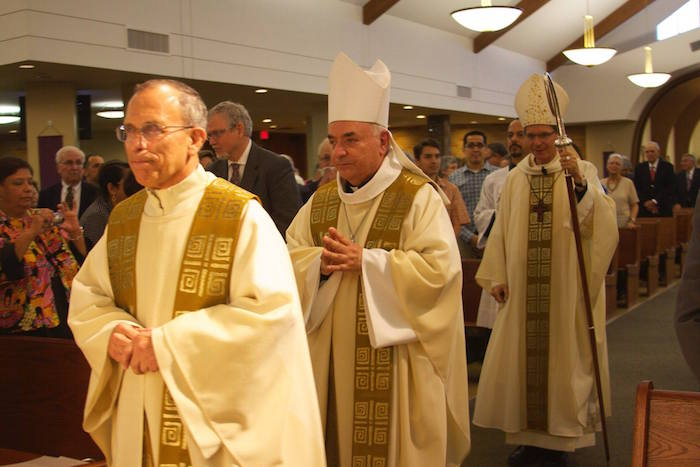 Father Garcia in the procession at the end of mass at St. Luke's Catholic Church. Photo by Felix Diaz.
