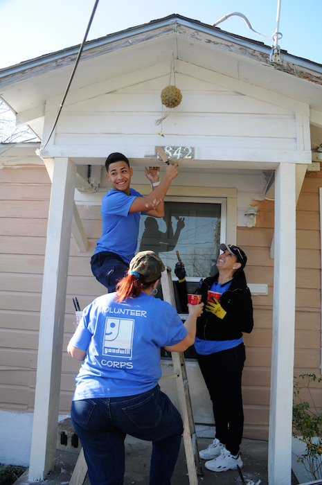 Geraldo Arredondo works on the entrance of a house during the EastPoint Shine Paint-A-Thon. Photo by Kristian Jaime.