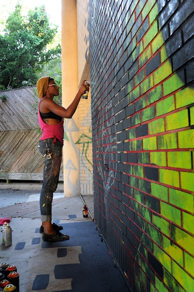 Roshi K applies aerosol paint to her mural. Often, murals requires days and hours of concentration. Photo by Danny Vivian.