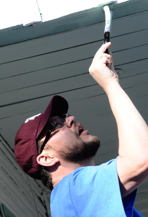 James Hughes paints the tough spots during the EastPoint Shine Paint-A-Thon. Photo by Kristian Jaime.