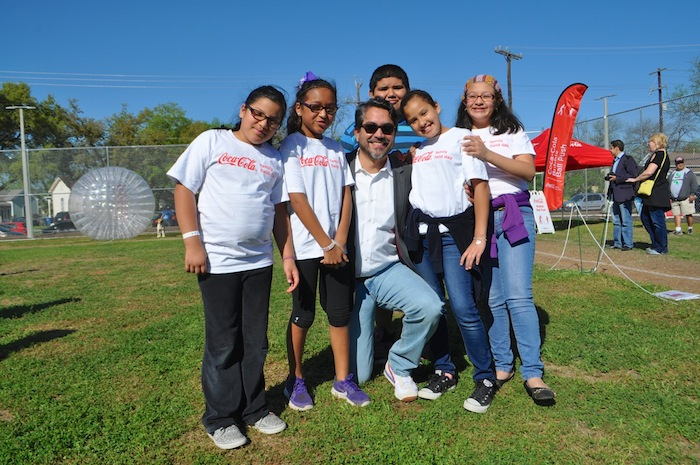 Councilmember Roberto Treviño poses for a photo with a group of kids during the Labor Street Park grand opening. Photo by Iris Dimmick.