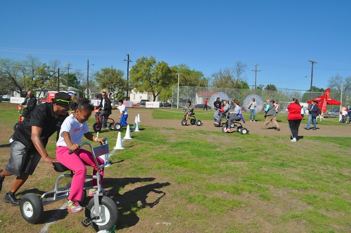 Kids and parents race tricycles during the Labor Street Park grand opening. Photo by Iris Dimmick.