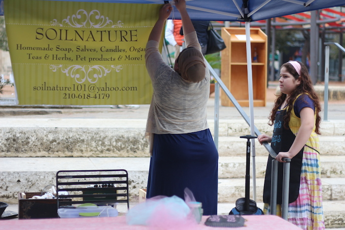 Kelly Diaz and her daughter, Gianni, set up their Soilnature shop at the Main Plaza Farmers Market on Tuesday. Photo by Joan Vinson.
