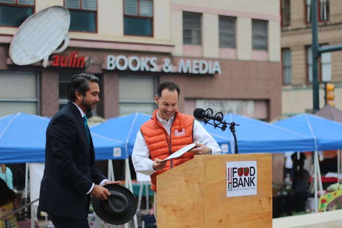 San Antonio Food Bank President Eric Cooper passes on his place at the podium to Councilmember Roberto Trevino (D1). Photo by Joan Vinson.