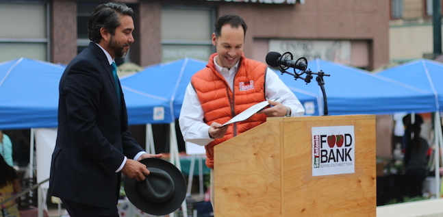 San Antonio Food Bank President Eric Cooper passes on his place at the podium to Councilmember Roberto Treviño (D1). Photo by Joan Vinson.