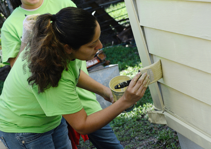 Maria Avalos puts the finishing touches on her work at the EastPoint Shine Paint-A-Thon. Photo by Kristian Jaime.
