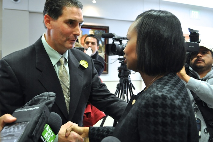 Yellow Cab San Antonio President John Bouloubasis shakes hands with Mayor Ivy Taylor after the City Council vote to approve revisions to rideshare regulation. Photo by Iris Dimmick.
