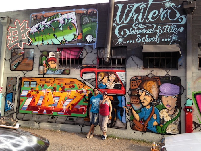 The artist Triz (right) and her crew member (left) stand next to a finished mural that was done during a local festival called Content Under Pressure. Courtesy Photo.