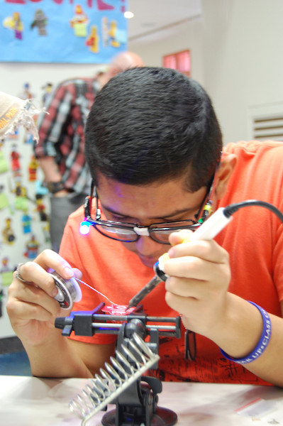 A teen learns to use a soldering machine during Teen Tech Week at the San Antonio Public Library. Photo Courtesy of Teen Services at the San Antonio Public Library.