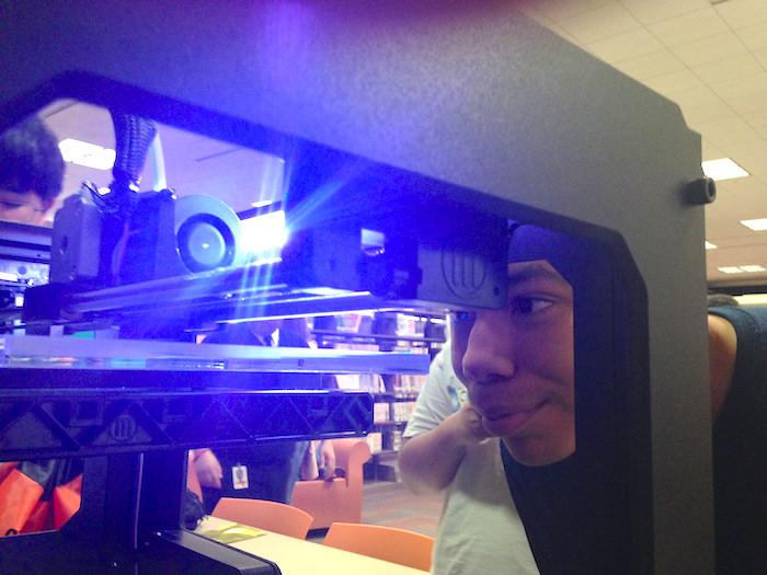 A teen watches his creation come to life on a 3D printer during Teen Tech Week at the San Antonio Public Library. Photo Courtesy of Teen Services at the San Antonio Public Library.