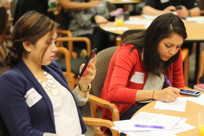 Attendees take notes and check social media during a 15-minute break at the women in media workshop on Thursday. Photo by Joan Vinson.