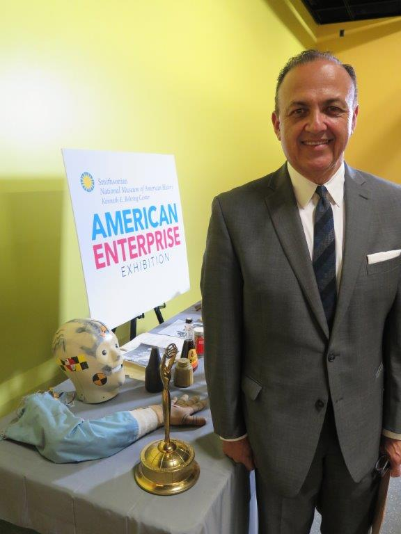 """Al Aguilar poses for a photo with the Smithsonian exhibit """"American Enterprise."""" Photo courtesy of Creative Civilization."""