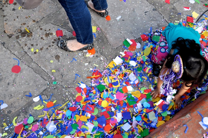 A young girl reuses piles of confetti to surprise unsuspecting passersby. Photo by Iris Dimmick.