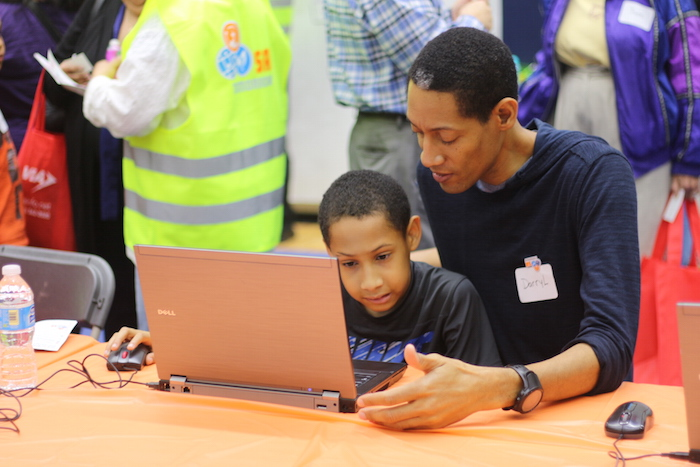 A father and son answer questions on a computer during the SA Tomorrow kickoff at the Alamo Convocation Center. Photo by Joan Vinson.