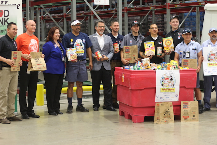 """Gould, Guerra, Fish, and their collective team pose for a photo during a """"Stamp Out Hunger"""" kickoff event at the San Antonio Food Bank. Photo by Joan Vinson."""