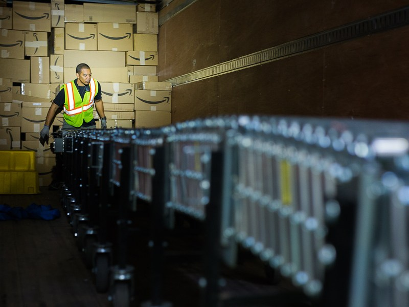 An Amazon worker organizes packages in a shipping container at the Amazon Fulfillment Center. Photo by Scott Ball.