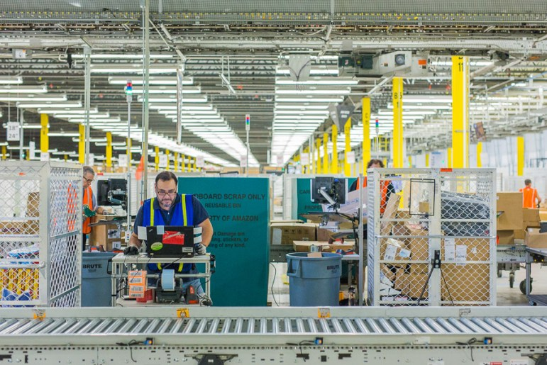 Workers scan in packages at the Amazon Fulfillment Center in Shertz.