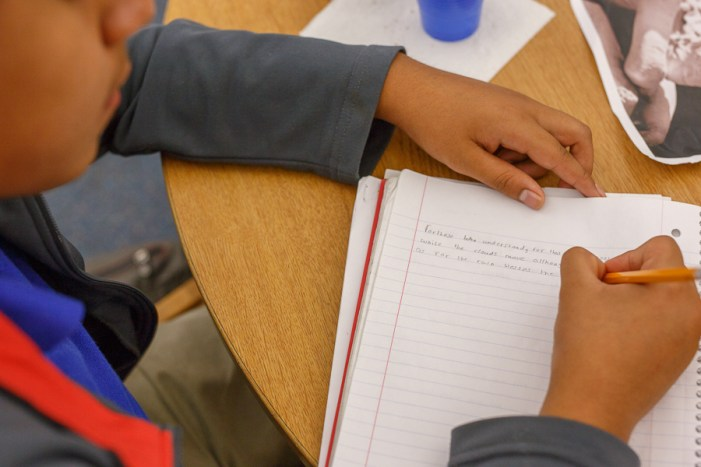 A student writes out a poem at a poet workshop hosted by Naomi Shihab Nye at Lanier High School. Photo by Scott Ball.