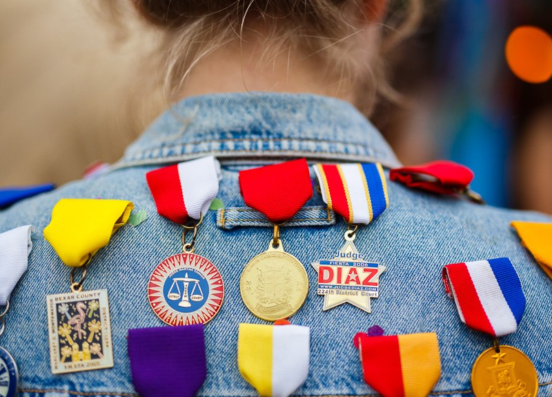 A woman shows off her jean vest full of Fiesta medals during NIOSA 2015 at La Villita. Photo by Scott Ball.