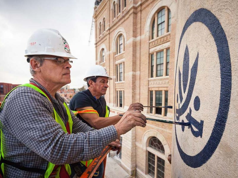 Finishing touches are made to Southerleigh's hand-painted logo on the historic silos. Photo by Scott Martin.