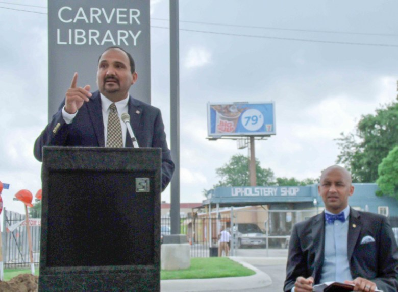 San Antonio District 2 City Councilman Alan Warrick (right) listens as assistant city engineer Ruben Guerrero speaks at a shovel-turning ceremony Wednesday at the Carver Library branch for the East Commerce improvement project.